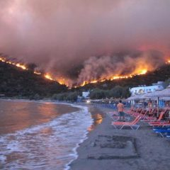 epa03364503 Citizens of the village of Lithi find refuge at the beach as a wildfire burns on a mountain next to it, in the island of Chios, Greece, 18 August 2012.  EPA/ALEXANDROS VLACHOS